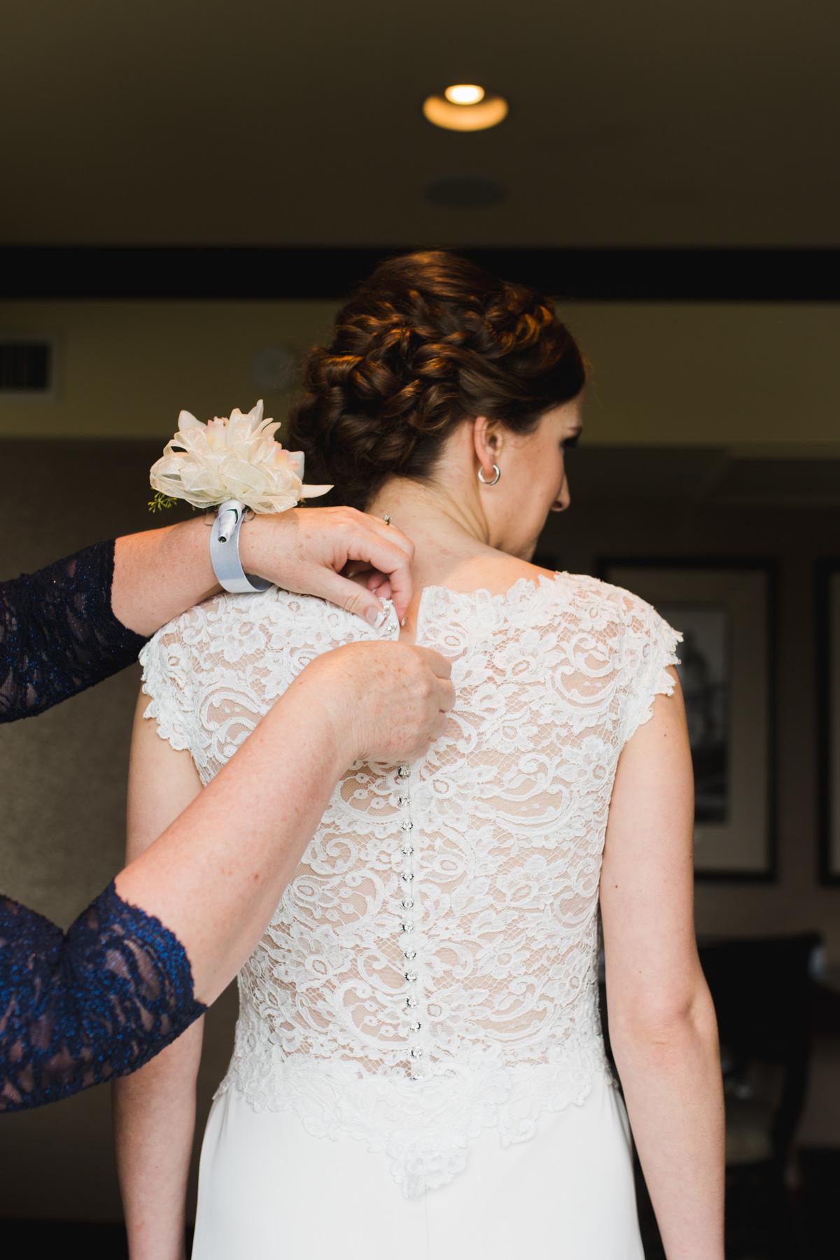 white wedding dress being zipped